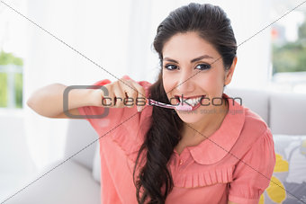 Cheerful brunette sitting on her sofa brushing her teeth