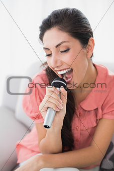 Brunette sitting on her sofa singing into microphone