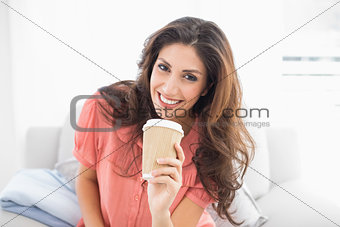 Smiling brunette sitting on her sofa holding disposable cup