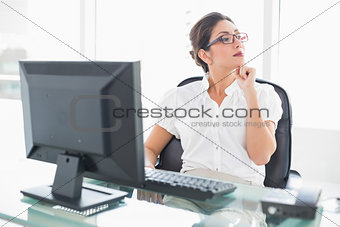 Thoughtful businesswoman sitting at her desk looking away