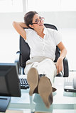 Relaxed businesswoman sitting at her desk with her feet up smiling at camera