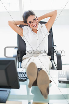 Relaxed businesswoman sitting at her desk with her feet up looking at camera