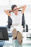Reclining businesswoman sitting at her desk with her feet up