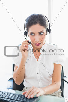 Serious call centre agent working at her desk on a call