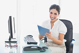 Happy businesswoman using her digital tablet at desk