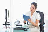 Focused businesswoman using her digital tablet at desk
