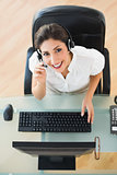 Cheerful call center agent looking at camera while on a call