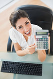 Smiling accountant holding a calculator looking at camera