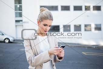 Thoughtful stylish businesswoman sending a text