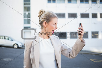 Angry stylish businesswoman shouting at her phone
