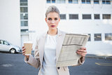Serious stylish businesswoman holding newspaper and coffee