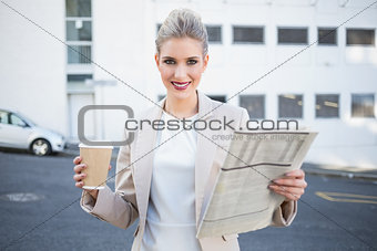 Smiling stylish businesswoman holding newspaper and coffee