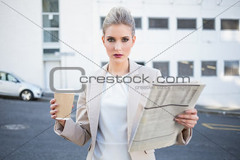 Stern stylish businesswoman holding newspaper and coffee