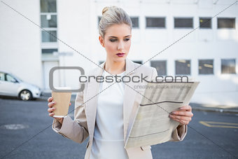 Stern stylish businesswoman reading newspaper