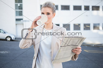 Serious stylish businesswoman drinking coffee
