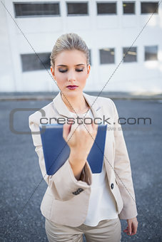 Serious stylish businesswoman holding tablet computer