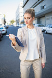 Stern classy businesswoman holding tablet computer