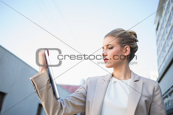 Low angle view of classy businesswoman holding tablet computer