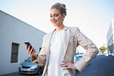 Smiling elegant businesswoman looking at her smartphone