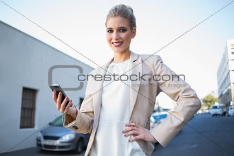 Cheerful elegant businesswoman holding smartphone