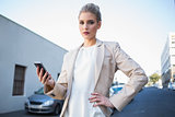 Stern elegant businesswoman holding smartphone