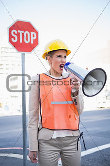 Angry businesswoman wearing builders clothes shouting in megaphone