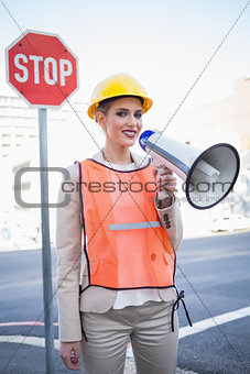 Smiling businesswoman wearing builders clothes shouting in megaphone