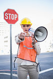 Businesswoman wearing builders clothes pointing at camera