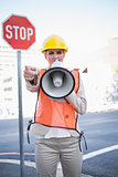 Businesswoman wearing builders clothes screaming in megaphone
