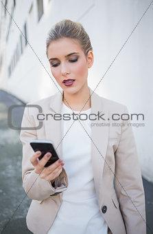 Serious attractive businesswoman sending a text