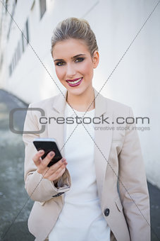 Smiling attractive businesswoman sending a text