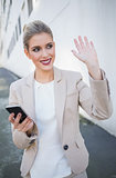 Smiling attractive businesswoman waving