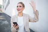 Cheerful attractive businesswoman waving