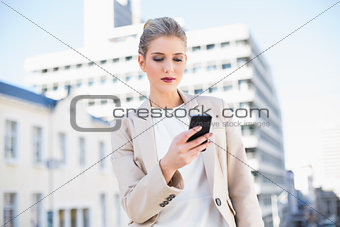 Peaceful attractive businesswoman sending a text message