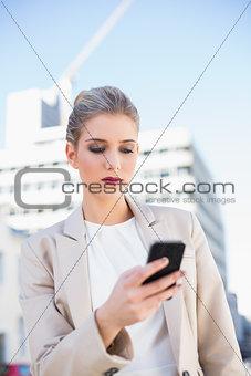 Serious attractive businesswoman sending a text message