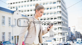 Focused gorgeous businesswoman text messaging