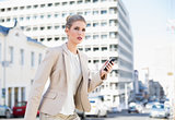 Frowning gorgeous businesswoman text messaging