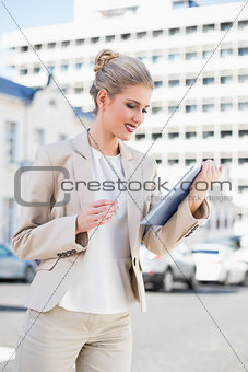 Smiling gorgeous businesswoman using tablet pc