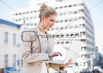 Smiling gorgeous businesswoman working on laptop