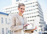 Happy gorgeous businesswoman working on laptop