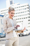 Smiling elegant businesswoman working on laptop