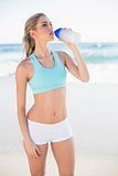 Gorgeous sporty blonde in sportswear drinking water