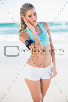 Peaceful sporty blonde in sportswear listening to music