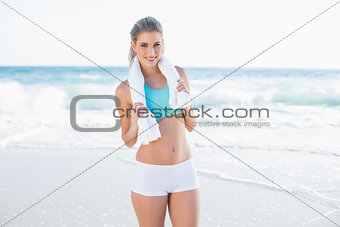 Cheerful sporty blonde in sportswear with towel around neck