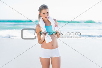 Serious sporty blonde in sportswear with towel around neck