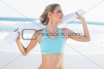 Smiling sporty blonde in sportswear holding towel