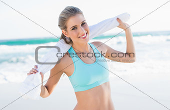 Cheerful sporty blonde in sportswear holding towel