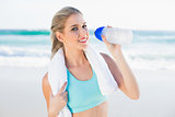 Smiling fit blonde in sportswear drinking water