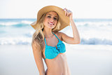 Cheerful sexy blonde in bikini wearing straw hat