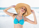 Peaceful sexy blonde in bikini wearing straw hat